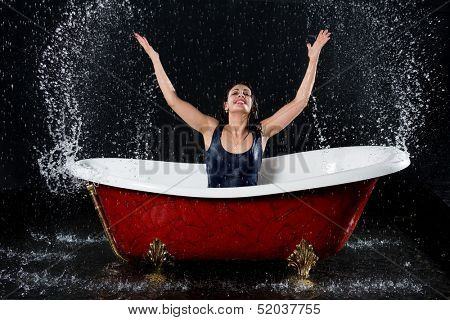 Drenched girl splashes water in the bathtub under the spray