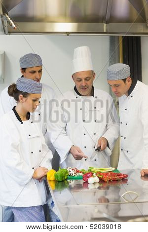 Smiling head chef teaching how to chop vegetables to students in busy kitchen