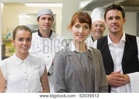 Young female manager posing in a modern kitchen with the staff