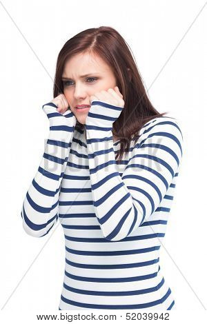Apprehensive young brunette posing on white background