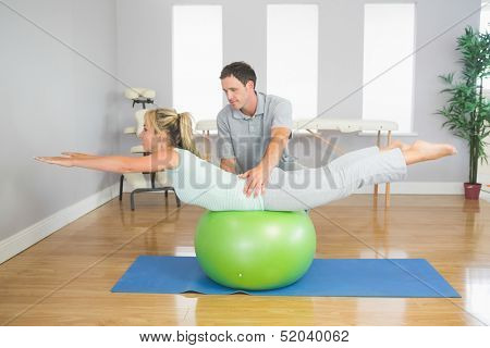 Physiotherapist helping patient doing exercise with exercise ball in bright room