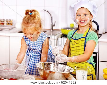 Child with rolling-pin dough at kitchen.