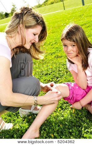 Mother Putting Bandage On Child