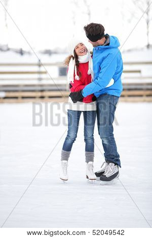 Ice skating couple on date in love iceskating and embracing. Young couple embracing on ice skates outdoors on open air rink in snowy winter landscape. Multiracial couple, Asian woman, caucasian man.