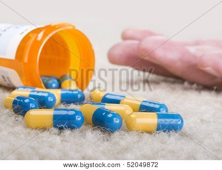 A person overdoses on prescription medication and lies unconscious on the floor
