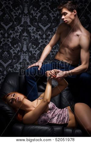 Young couple in bdsm action on the leather sofa
