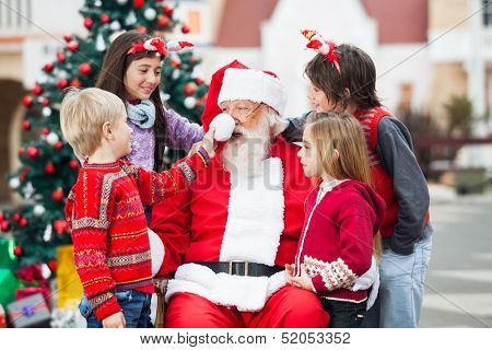 Children playing with Santa Claus's hat in courtyard