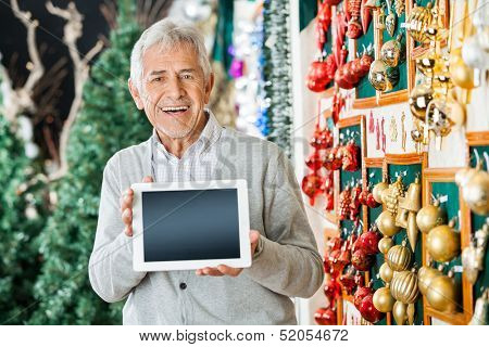 Portrait of happy senior man holding digital tablet while standing at Christmas store