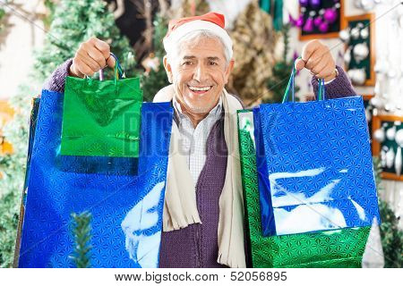 Portrait of happy senior man carrying shopping bags at Christmas store