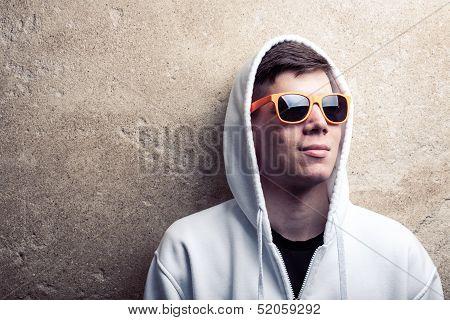 Street Portrait Of Young Boy In White Sweatshirt With Orange Modern Eyeglasses And Hood