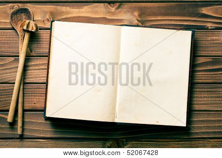 top view of recipe book with stirring spoons