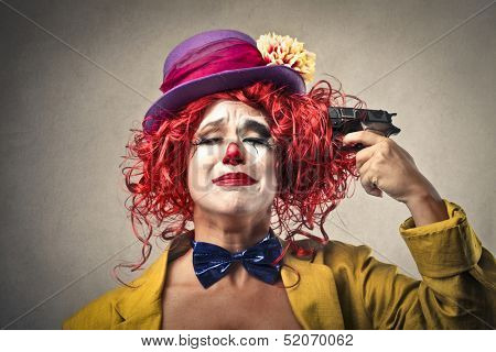 beautiful clown is pointing a gun to her head