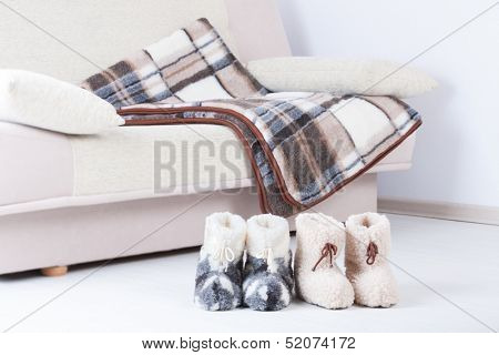 Two pair of natural woollen slippers on wooden floor and blanket on the couch