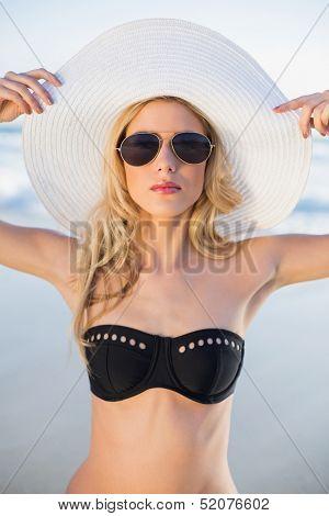 Serious sensual blonde in elegant black bikini posing on a beautiful sunny beach