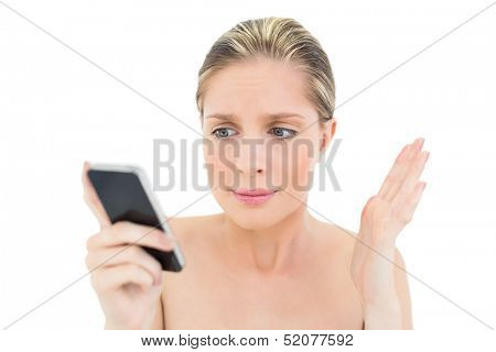 Puzzled fresh blonde woman looking at her mobile phone on white background