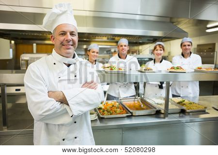 Proud mature head chef posing in a modern kitchen with his colleagues in the background