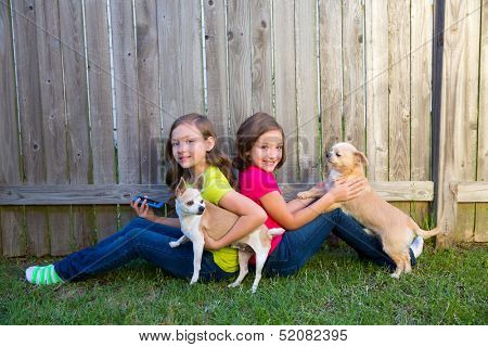 Twin sister girls playing with smartphone and chihuahua dog sitting on backyard