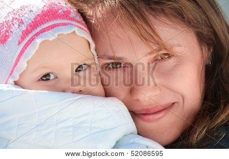 Young European Woman Holds Her Sleepy Baby In Blanket. Outdoor Closeup Portrait