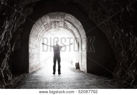 Man Stands In Dark Tunnel With Glowing End