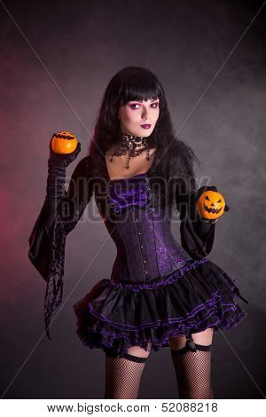 Smiling witch in purple gothic Halloween costume holding Jack-o-lantern style oranges