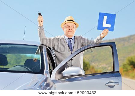 Smiling senior man posing next to his car holding a L sign and car key after having his driver's licence, outside