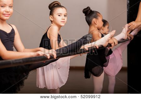 Pretty little dancers using a barre