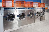 stock photo of laundromat  - Washing machines and empty baskets in a row at laundromat - JPG
