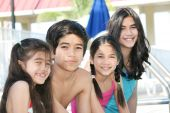 stock photo of family fun  - Four smiling children enjoying the pool together - JPG