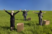 image of thinking outside box  - Concept shot showing three business executives one male and two female standing outside boxes in a green field and raising their arms towards the horizon - JPG