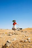 foto of megaliths  - young woman bouncing on Zorats Karer  - JPG