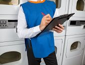 stock photo of laundromat  - Midsection of male helper writing on clipboard in laundromat - JPG