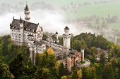 stock photo of castle  - Neuschwanstein Castle shrouded in mist in the Bavarian Alps of Germany - JPG