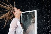 Wet girl with disheveled hair under the spray of water near the mirror