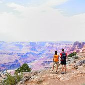 Grand Canyon - people hiking looking at view. Hiker couple walking on South Rim trail of Grand Canyo