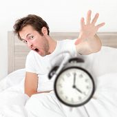 Man waking up late for work early throwing alarm clock. Funny bed concept with young man oversleepin