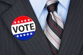 A politician wearing his lapel voting pin on his elegant business suit.