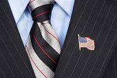 A symbolic American flag lapel pin on the collar of a businessman's suit