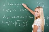 foto of clever  - Clever confident female student in the classroom writing on a chalkboard completing mathematical equations - JPG