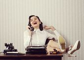 stock photo of secretary  - Cheerful woman talking on phone at desk - JPG