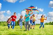 stock photo of kites  - Happy little smiling boy with kite running in the park with kite and group of friends in the park on sunny summer day - JPG