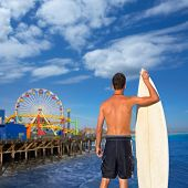 Boy surfer back rear view holding surfboard on santa Monica Pier California