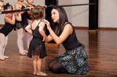 stock photo of ballet barre  - female dance instructor comforting one of her ballet students during a dance class - JPG