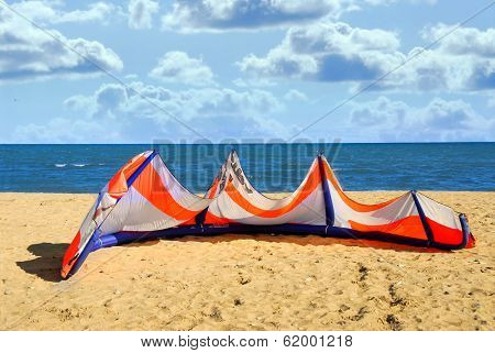 Big kite for kite surfing lying on a sandy beach