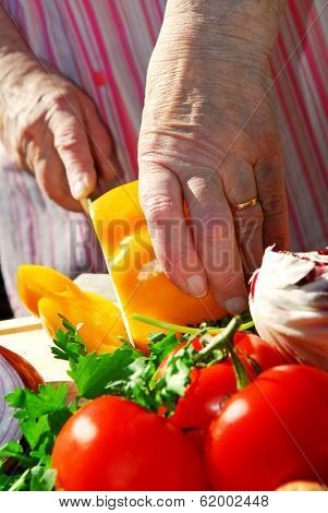 Hands of an elderly woman cutting fresh vegetables