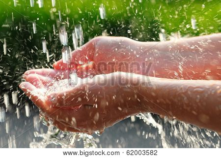 Hands catching clean falling water close up. Environmental concept.