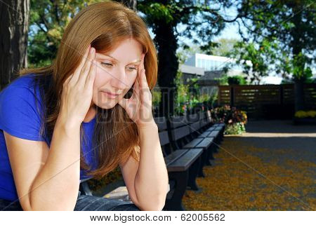 Mature woman with a headache sitting on the park bench