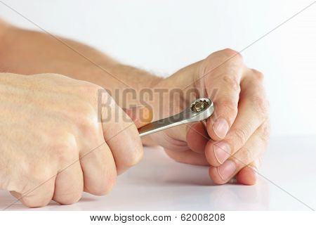 Hand with a wrench to tighten the nut