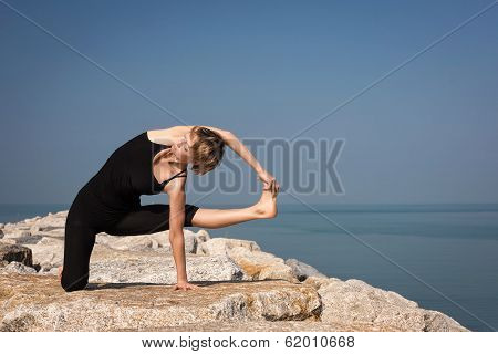 Beautiful woman practicing yoga at seashore.