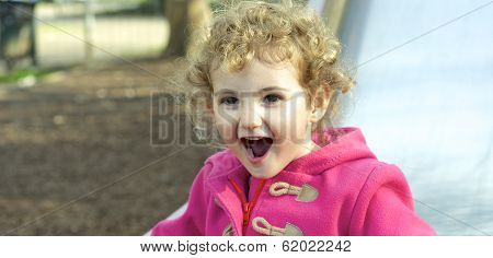 Pretty young child having fun on a slide.