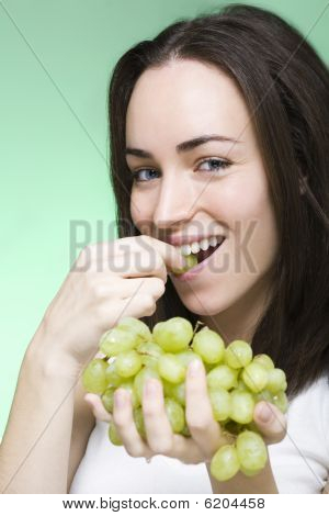 Young Woman Bites Into Grape And Smiles